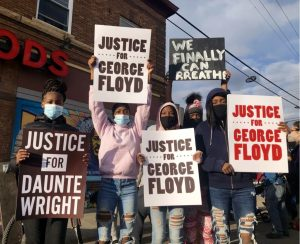 Several demonstrators holding signs demanding justice for George Floyd