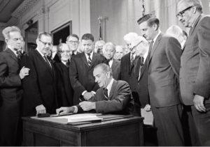 President Lyndon Johnson signs the Civil Rights Act as Senators look on