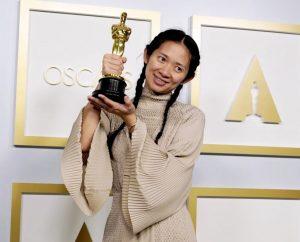 Chloe Zhao holding up Oscar